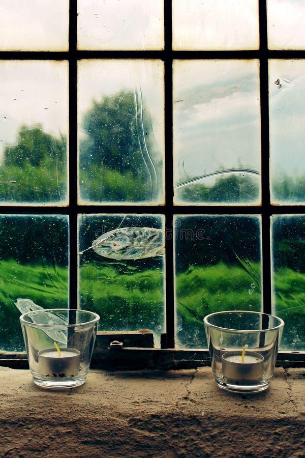 2 candele di Tealight sul vetro di finestra fotografia stock
