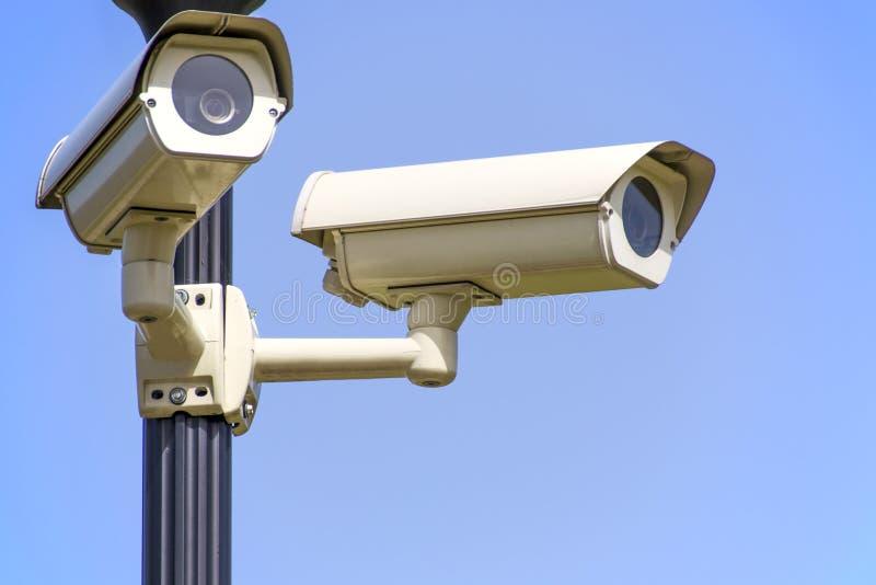 白色2在黑岗位登上的Cctv照相机在清楚的蓝天下 免版税库存图片