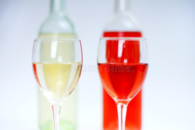 2 glazen van wit en namen wijn met flessen en witte achtergrond toe stock foto's