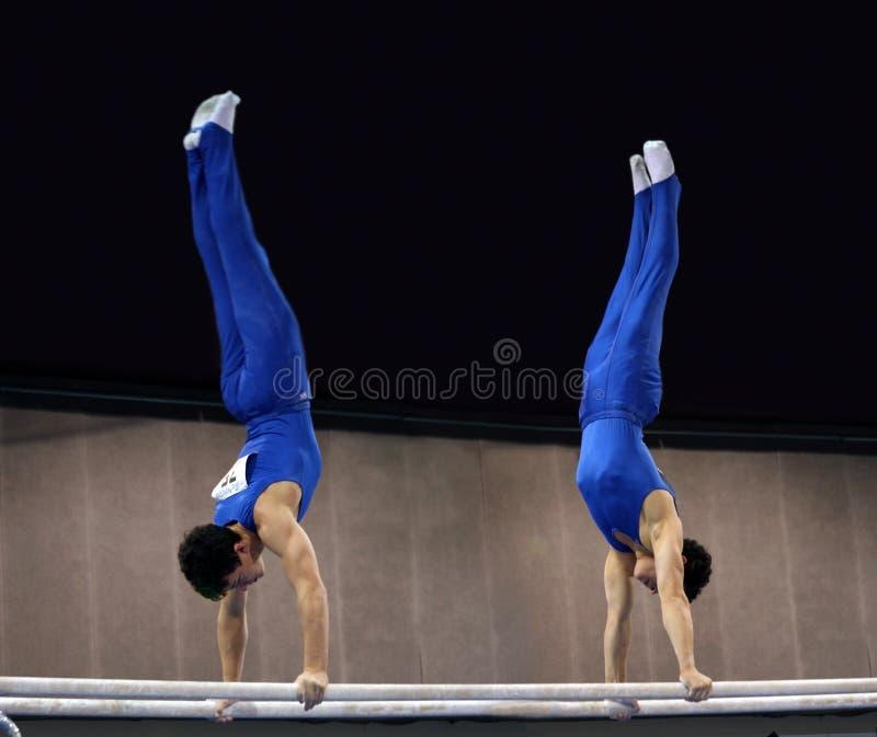 2 Gymnastes Sur Les Bars Parallèles Image stock