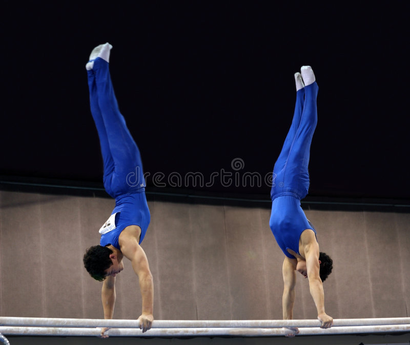 2 Gymnasts Sulle Barre Parallele Immagine Stock