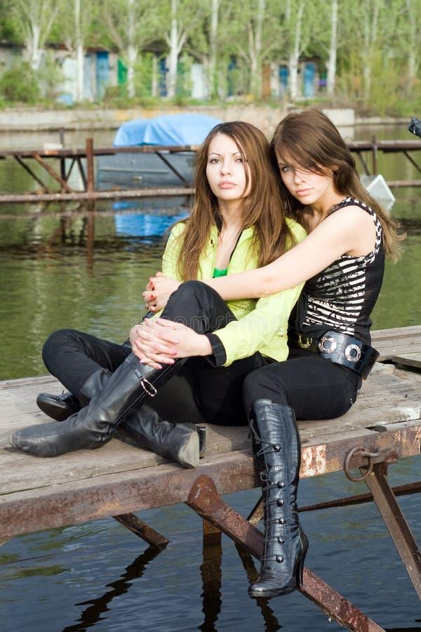 2 härliga omfamna flickor som förtöjer två royaltyfria foton