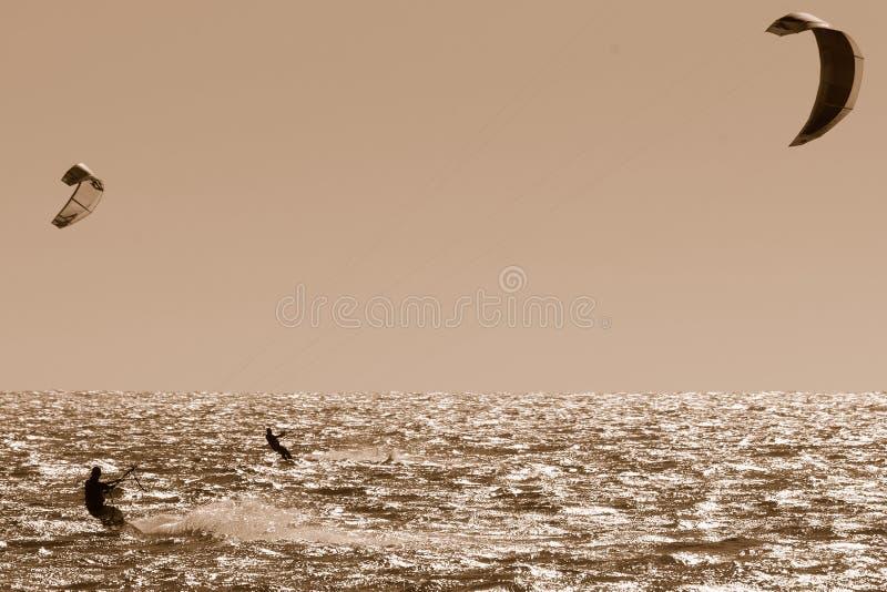 2 Kite Surfers In Sepia Stock Image
