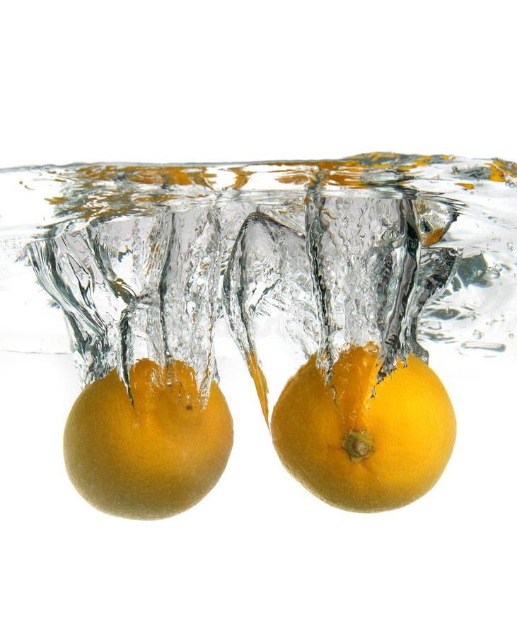 2 lemons dropped in water. Crating splash royalty free stock photos
