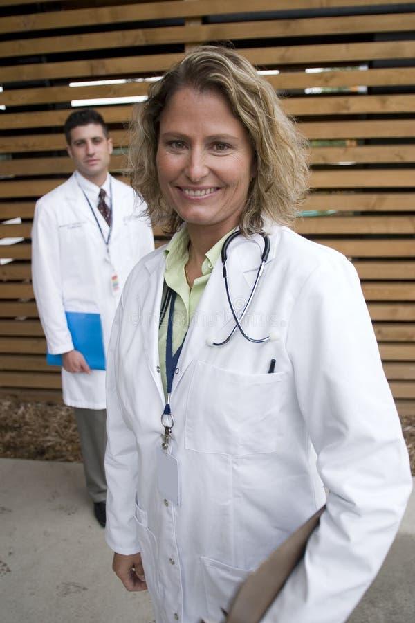 2 medici fuori dell'ospedale contro la parete fotografia stock libera da diritti