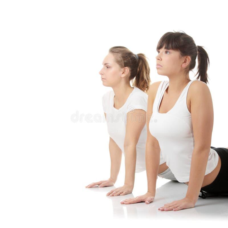 2 mooie jonge womans die yogaoefening doen royalty-vrije stock fotografie