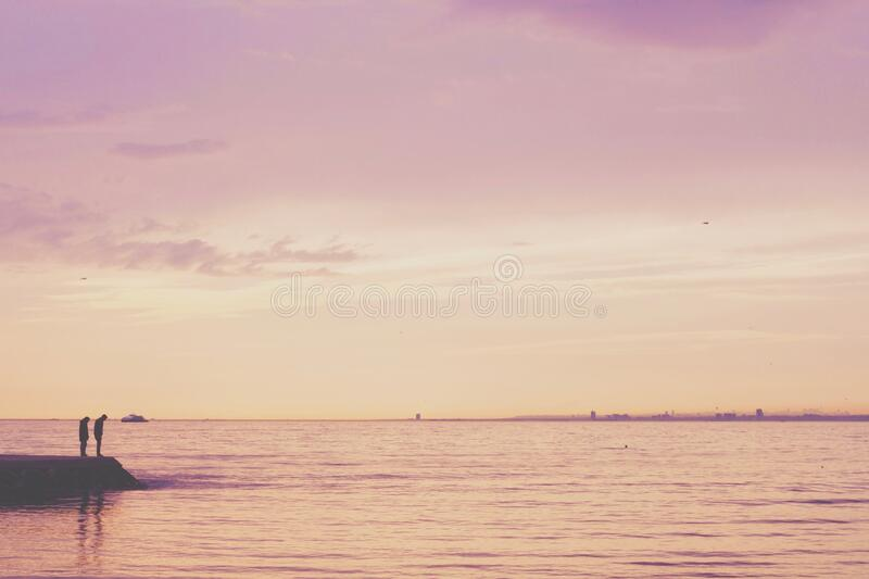 2 Person Standing auf Ufer nahe ruhigem See stockbild