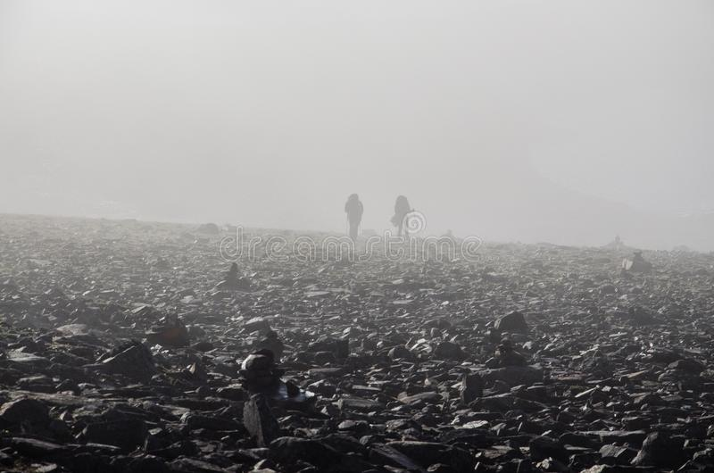 2 Persons Walking On Black Rock Under Fogs During Daytime Free Public Domain Cc0 Image