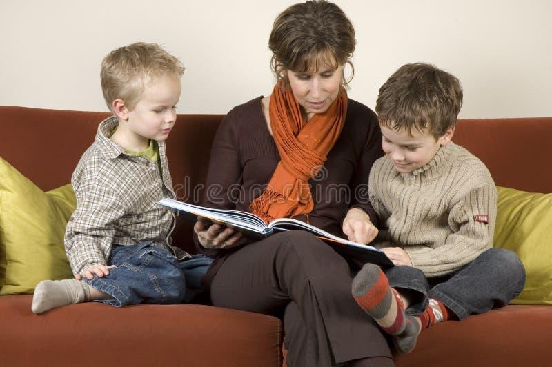 2 sons två för bokmoderavläsning royaltyfri bild