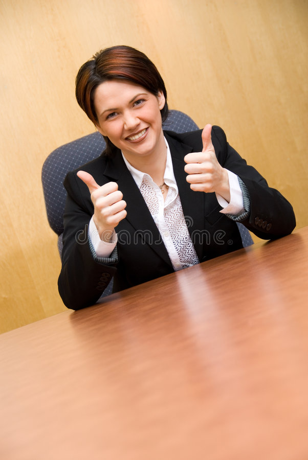 2 thumbs up!. Happy business woman in a boardroom table royalty free stock image