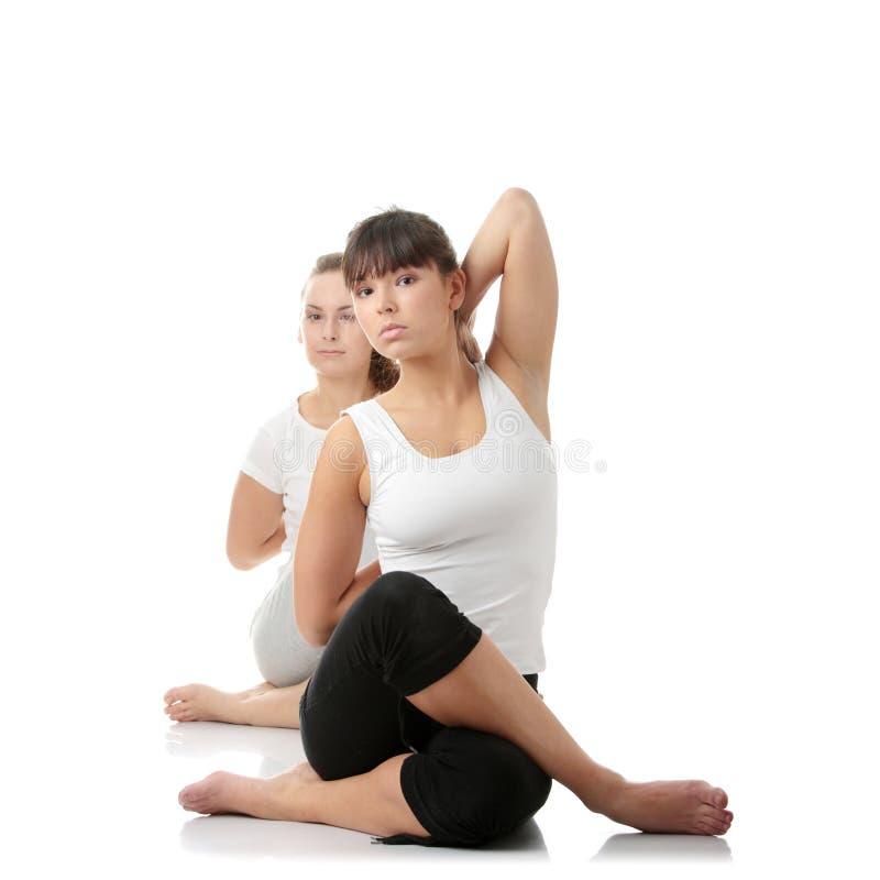 2 womans novos bonitos que fazem o exercício da ioga imagem de stock