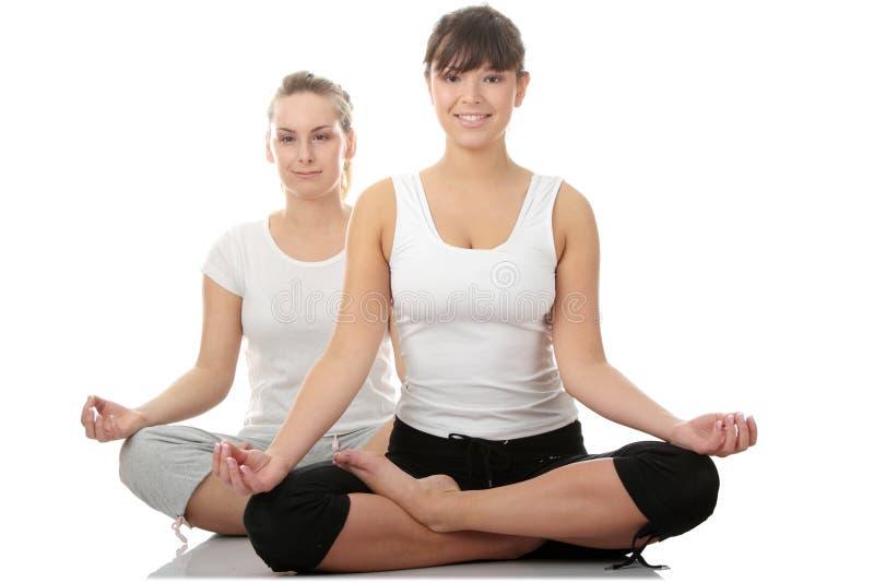 2 womans novos bonitos que fazem o exercício da ioga fotografia de stock