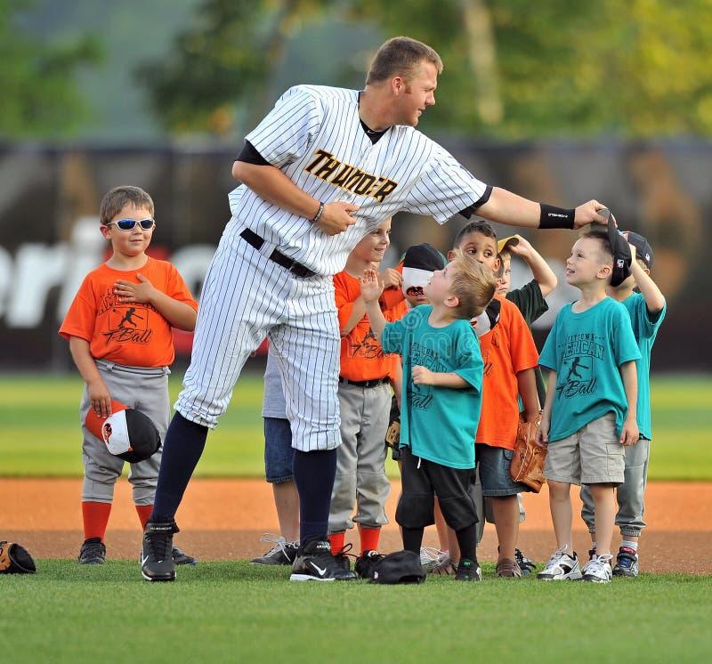 2012 Minor League Baseball. TRENTON, NJ - JUNE 19: Luke Murton, Trenton first baseman, playfully removes a child's hat during the National Anthem during the stock image