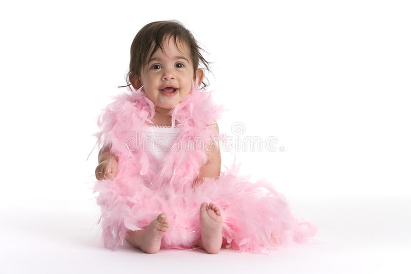 2090409-038. Baby Girl Sitting On The Floor Dressed In Pink Feathers Like A Diva stock image