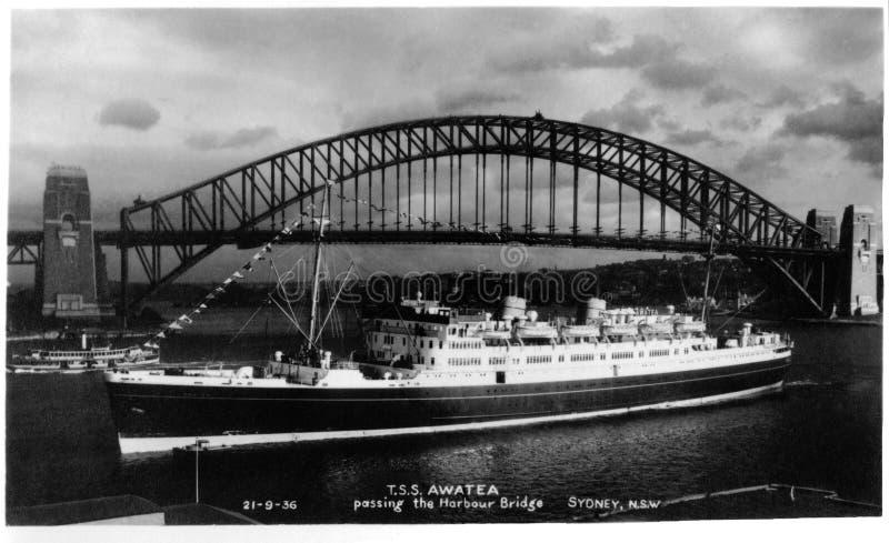 21 septembre 1936 - T S S Awatea passant le pont de port, Sydney - vraie carte postale de photo - version reconstituée image libre de droits