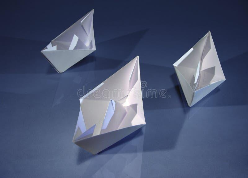 3 barcos de papel no azul imagens de stock royalty free
