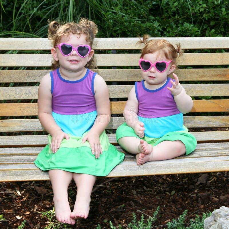 3 behandla som ett barn solglasögon två för klänningflickasunen royaltyfri fotografi