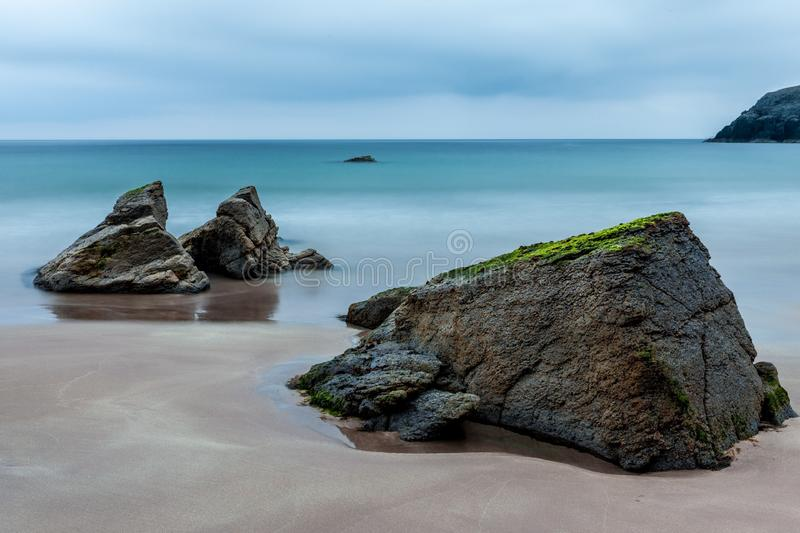 3 Brown Boulders on Seashore during Daytime royalty free stock photography