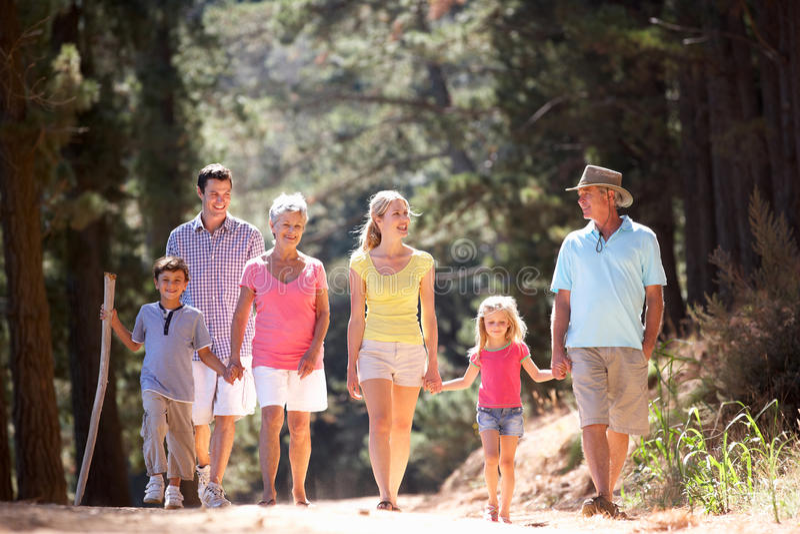 3 de familie die van de generatie langs landweg loopt stock fotografie