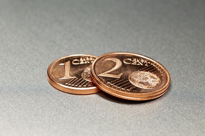 3 Euro Cents on a shiny alloy board. 1 Euro Cent and 2 Euro Cents on a shiny alloy board royalty free stock photos