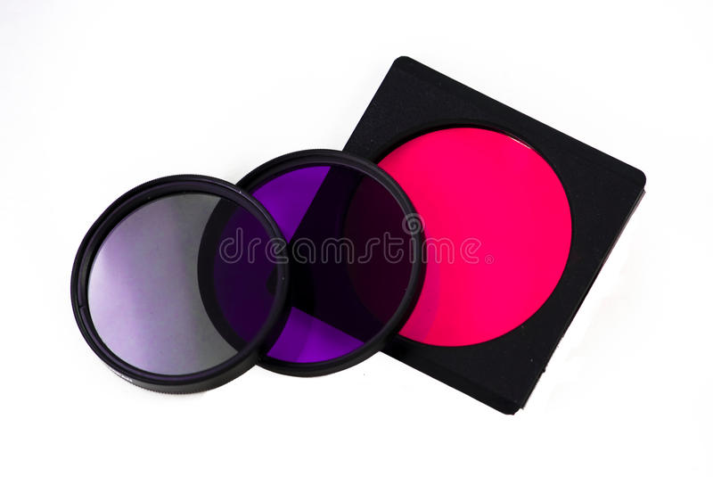 3 Filters. A set of assorted camera filters, one is a CPL and one is a purple intensifier and one is a pink gel in holder royalty free stock photos