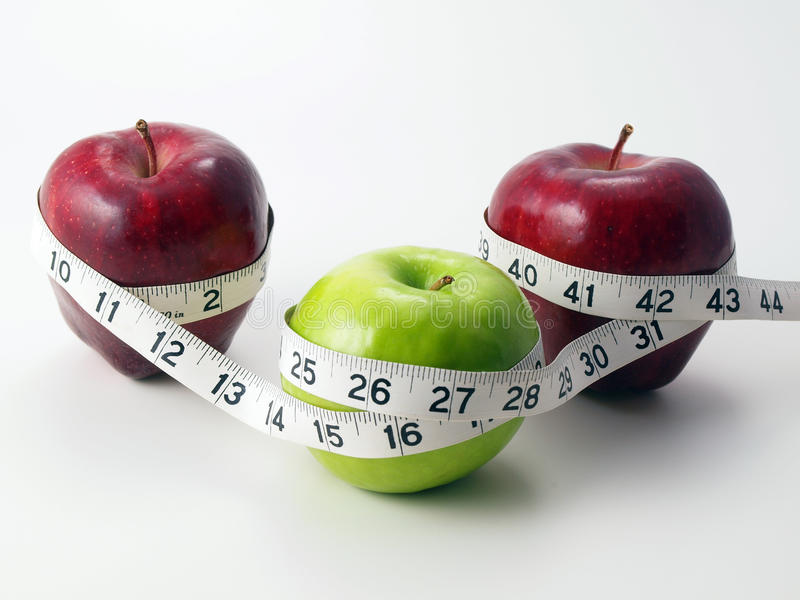 3 jabłka okrążali pomiarowej taśmy fotografia royalty free