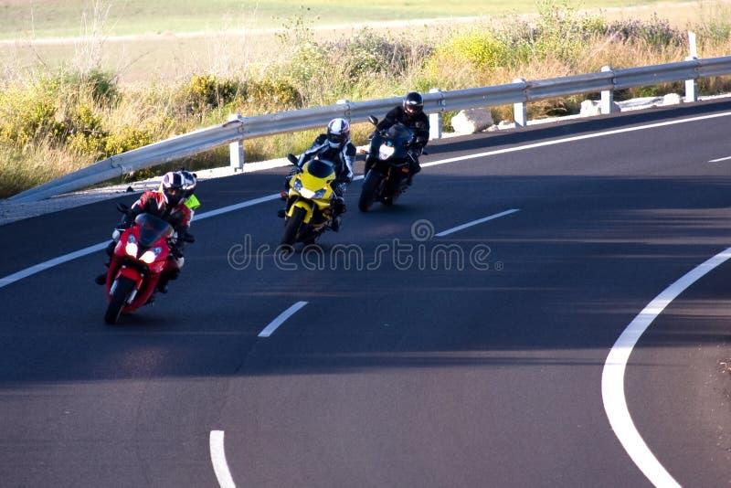 3 motociclisti sulla strada curva immagini stock libere da diritti