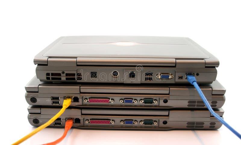 3 portáteis com cabos da rede fotografia de stock