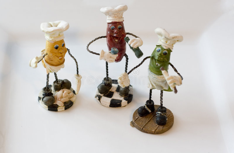3 small statues. 3 peppers standing with cooking impliments stock photos