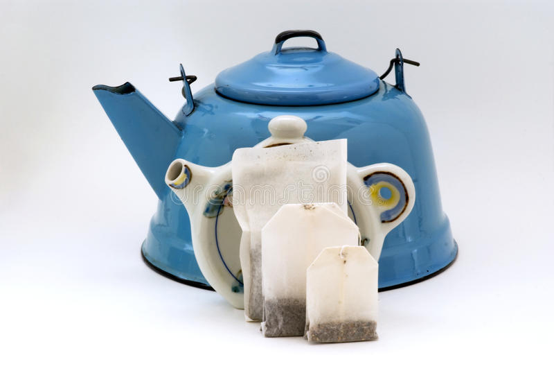 3 teabag sizes by teapot shape holder & teakettle. Blue enamel teakettle as background for teabags and vintage ceramic teabag holder stock photos