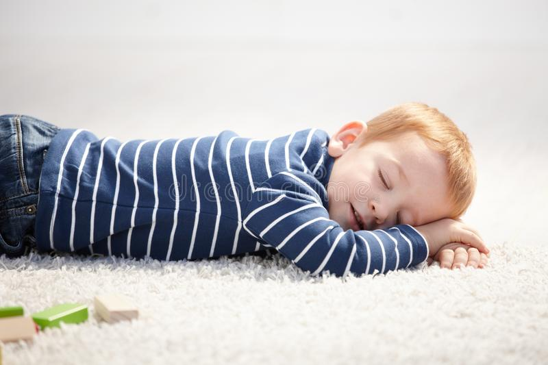 3 year old falling asleep on floor at home stock images