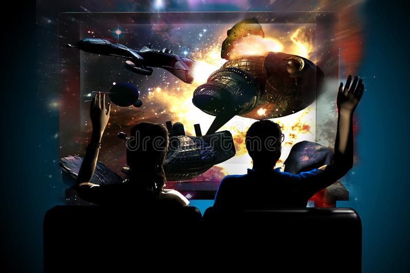 3D and 4k television. Sat in front of a 3D Led television with an image from a 3D science fiction movie where a spaceship is exploding, a man and a woman try to