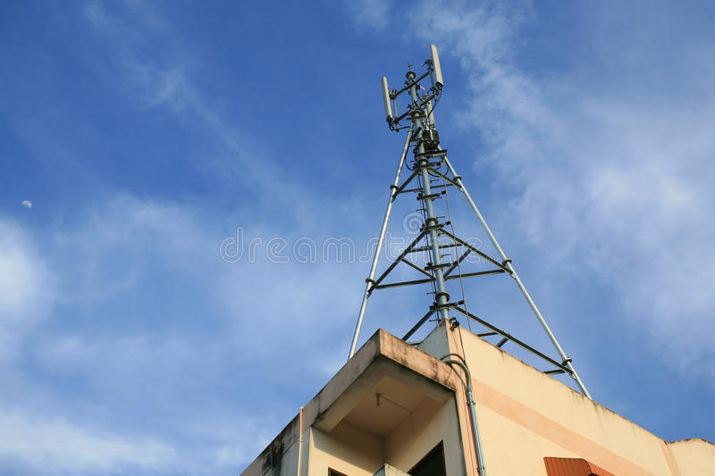 3G phone antenna mounted on top of building. Telecommunication: 3G phone antenna mounted on top of building against blue sky stock photos