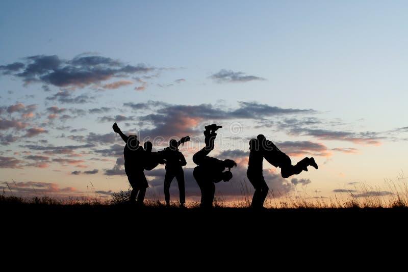 4 vänner som hoppar silhouettes arkivbilder