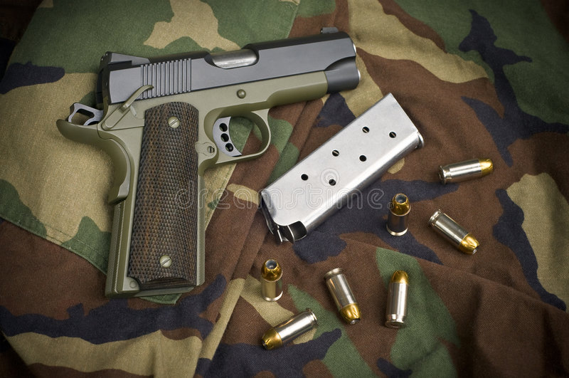 45 Firearm Pistol Clip And Hand Gun on Camouflage. 45 Firearm Pistol Clip And Hand Gun Ammunition on military camouflage background stock photo
