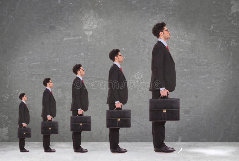 5 hombres de negocios que sostienen las carteras que se colocan en una fila fotos de archivo