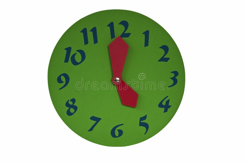5 o'clock. A green clock with red hands and blue numbers pointing at 5:00. Isolated on a white background royalty free stock images