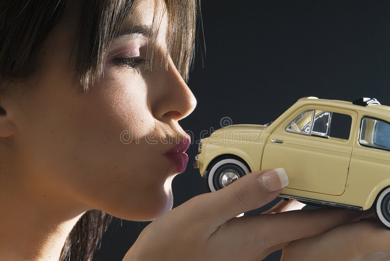 500 kiss. Nice and young brunette kissing with an italian style car,fiat 500 stock photography