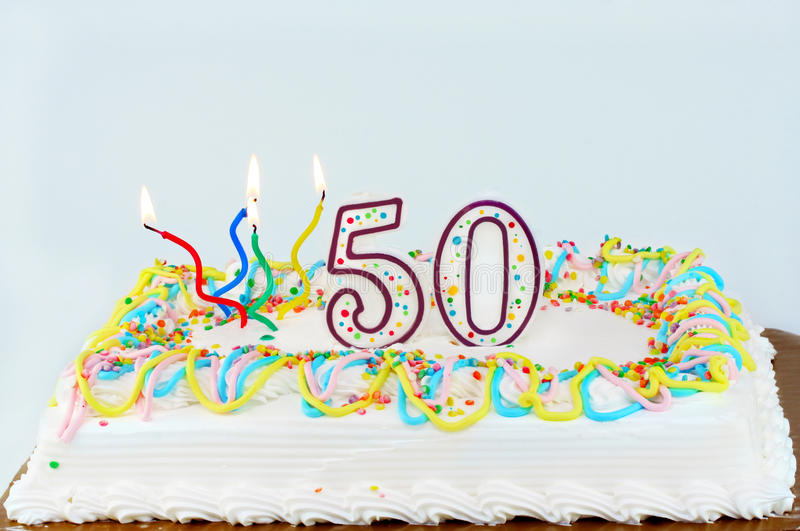 50th Birthday Cake. White frosted birthday cake with lit candles and the number 50 on top stock images