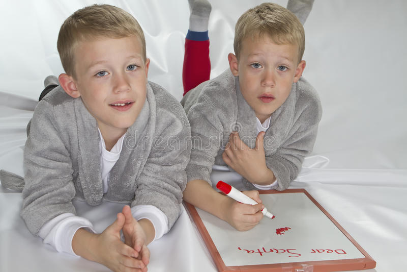 6 anos de gêmeos idênticos velhos que escrevem a letra a Sant imagem de stock royalty free