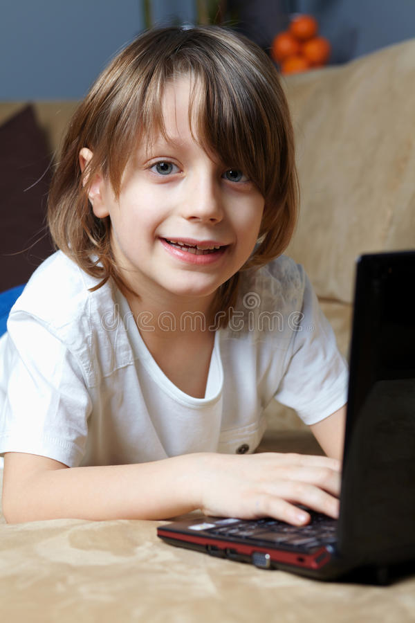 6 Year Old Boy Lying On The Sofa With His Laptop Stock Photos