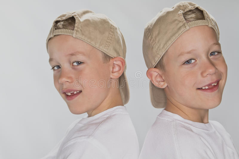 6 years old identical twins wearina a baseball hat stock photo