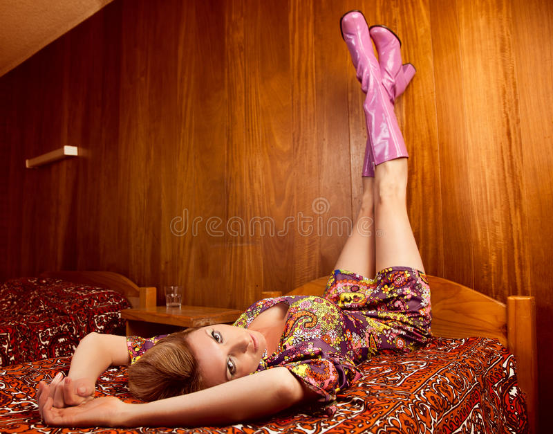 70s girl. 70's style - woman lying on a hotel bed with legs in the air stock photography