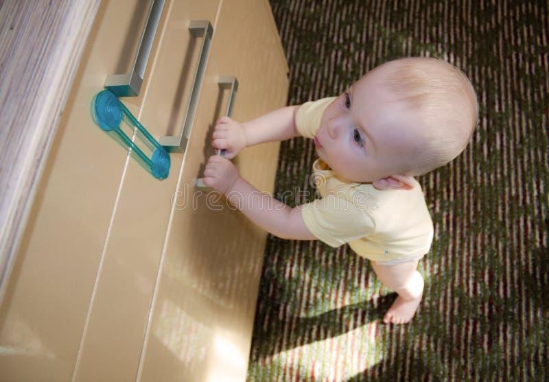 8 9 месяцев двери кухонного шкафа младенца раскрывают к пробовать стоковая фотография rf