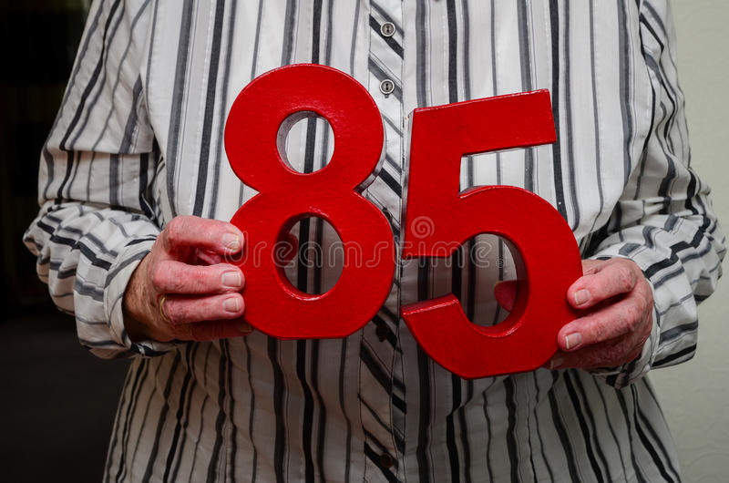 85th birthday. Senior woman holding red numbers for her eighty fifth birthday royalty free stock photo