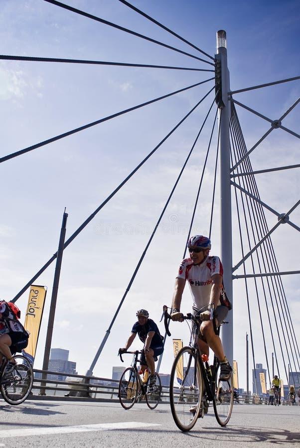 94.7 de Ruiters van de Uitdaging van de cyclus op de Brug van Mandela stock foto's