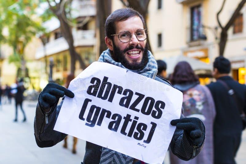 A ação de abraços livres de um grupo de pessoas nas ruas de Barcelona, a inscrição no espanhol em cartazes livra abraços fotografia de stock royalty free
