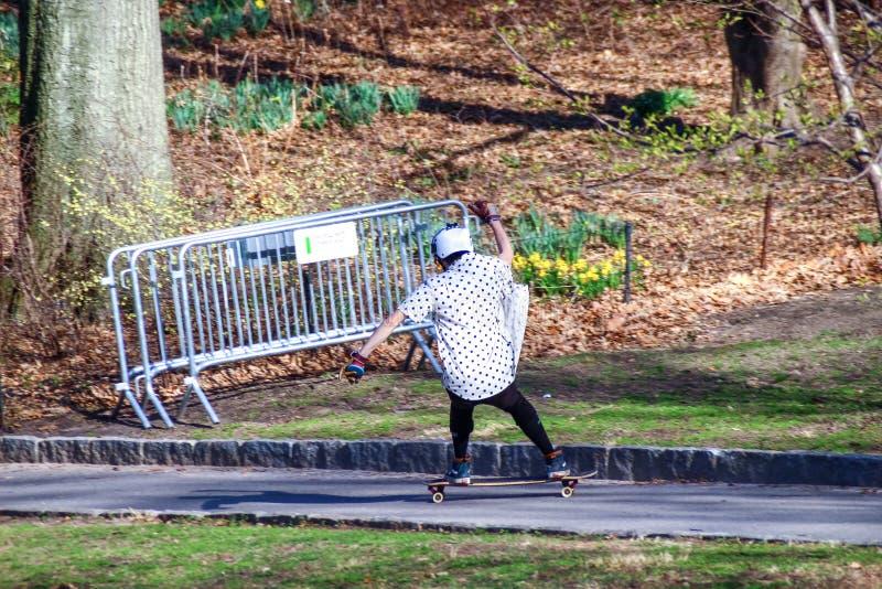 A ação disparou de um skater que patina na estrada através do Central Park Skate livre da equitação imagem de stock