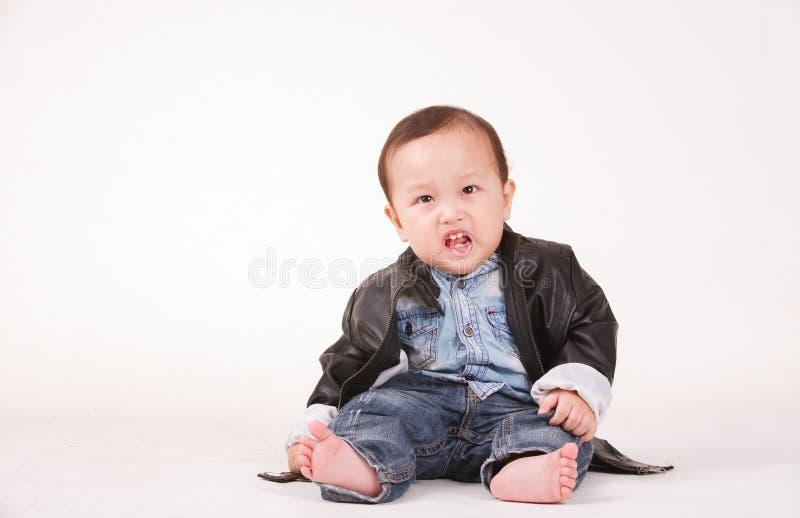 Ação irritada do retrato do bebê no casaco de cabedal, parte traseira do branco fotos de stock royalty free