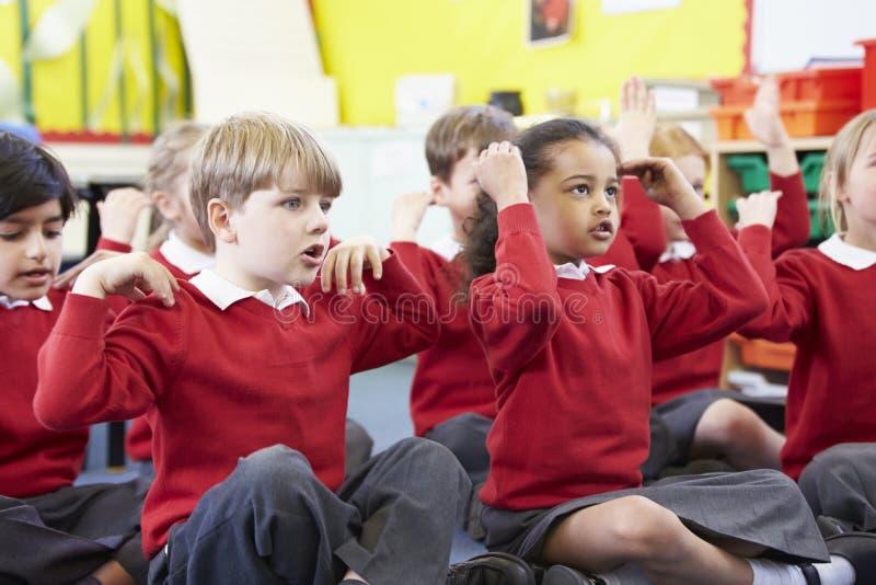 Ações de Perfoming dos alunos enquanto cantando a música imagens de stock